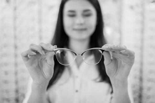 Black and white photo of girl holding glasses away form face inspecting them
